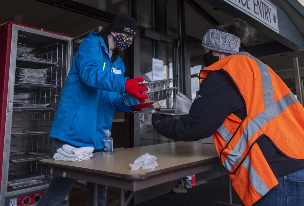 Taylor Scheetz, 14, left, hands packaged Thanksgiving meals to Sara Scheetz, both of Vancouver, during a Thanksgiving meal distribution event at WareHouse '23 in Vancouver. Owner Mark Matthias said the restaurant anticipated serving as many as 1,500 meals over the course of the day.