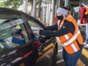 Sara Scheetz hands Thanksgiving dinners to a drive-thru visitor at WareHouse '23 in Vancouver. The restaurant's annual Thanksgiving Day meal service was restructured this year for delivery and curbside service.