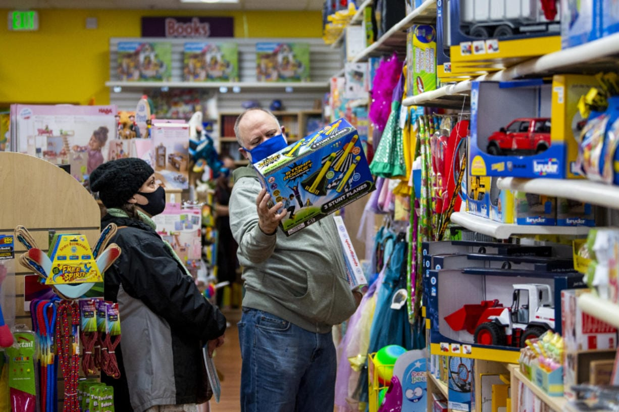 Christine Olsen, left, and Carl Olsen look for Christmas gifts for their kids on Saturday at Kazoodles toy store at Columbia Square in Vancouver. They went to Kazoodles to support small businesses.
