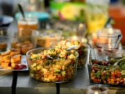 """Recipes from """"The Pickled Picnic."""" Foreground, left to right: Crispy Brine-Glazed Tofu, Pickled Three-Bean Salad, and Spiced Chickpeas With Fermented Rhubarb."""