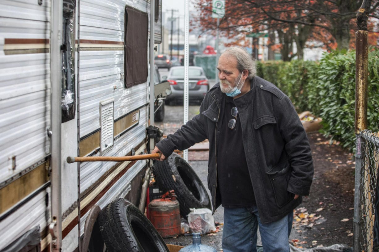 Joe Ingram, a member of the Scofflaw Mitigation Team, taps with his cane to rouse anyone inside this RV behind a Jack in the Box restaurant on First Avenue South in Seattle.