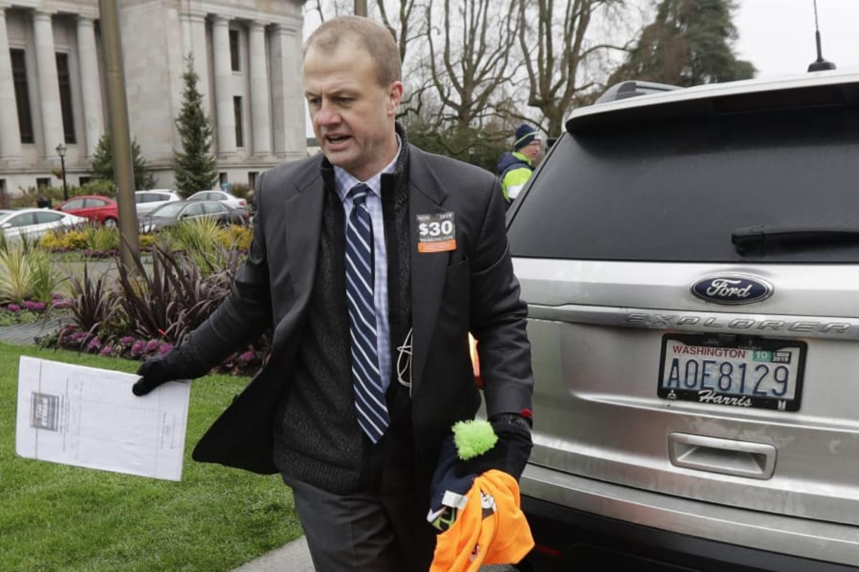 Initiative activist Tim Eyman, who was also running as an independent for Washington governor, carries a clipboard as he walks next to his expired car registration tabs Jan. 13 before attending a rally on the first day of the 2020 session of the Washington legislature at the Capitol in Olympia. (Ted S.