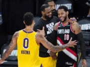 Los Angeles Lakers' Kyle Kuzma (0) and LeBron James, center, greet Portland Trail Blazers' Carmelo Anthony (00) after an NBA basketball first round playoff game Saturday, Aug. 29, 2020, in Lake Buena Vista, Fla. The Lakers won 131-122 to win the series 4-1.