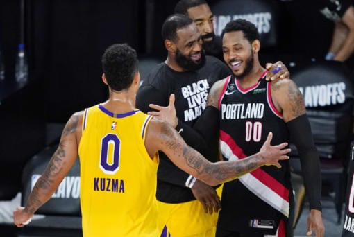 Los Angeles Lakers' Kyle Kuzma (0) and LeBron James, center, greet Portland Trail Blazers' Carmelo Anthony (00) after an NBA basketball first round playoff game Saturday, Aug. 29, 2020, in Lake Buena Vista, Fla. The Lakers won 131-122 to win the series 4-1. (AP Photo/Ashley Landis)