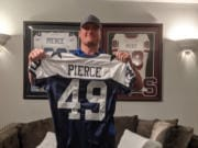 In his Dallas-area home, Brett Pierce holds his Dallas Cowboys jersey for the 2005 Thanksgiving Day game against the Denver Broncos.
