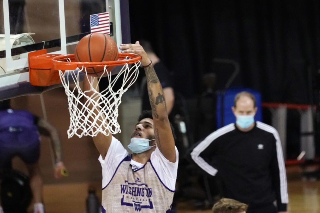 Washington forward J'Raan Brooks dunks as coach Mike Hopkins watches during a recent practice in Seattle. Brooks, a transfer from USC, is one of only three players on the Huskies roster who is 6-foot-9 or taller.
