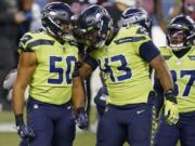 Seattle Seahawks outside linebacker K.J. Wright (50) and defensive end Carlos Dunlap (43) celebrate after a play against the Arizona Cardinals during the first half of an NFL football game, Thursday, Nov. 19, 2020, in Seattle.