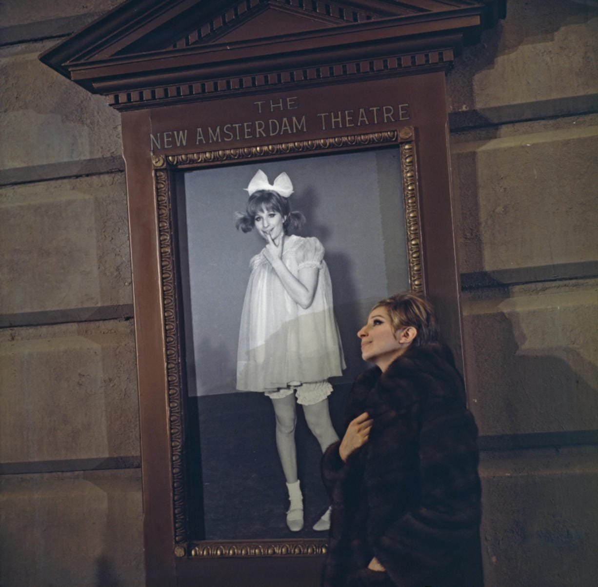 """Actress and singer Barbra Streisand outside the New Amsterdam Theatre in New York City in 1968, with a poster of herself in the movie """"Funny Girl."""" (Hulton Archive/Getty Images)"""