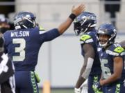 Seattle Seahawks quarterback Russell Wilson (3) celebrates with wide receiver DK Metcalf, center, after Wilson passed to Metcalf for a touchdown against the San Francisco 49ers during the first half of an NFL football game, Sunday, Nov. 1, 2020, in Seattle.