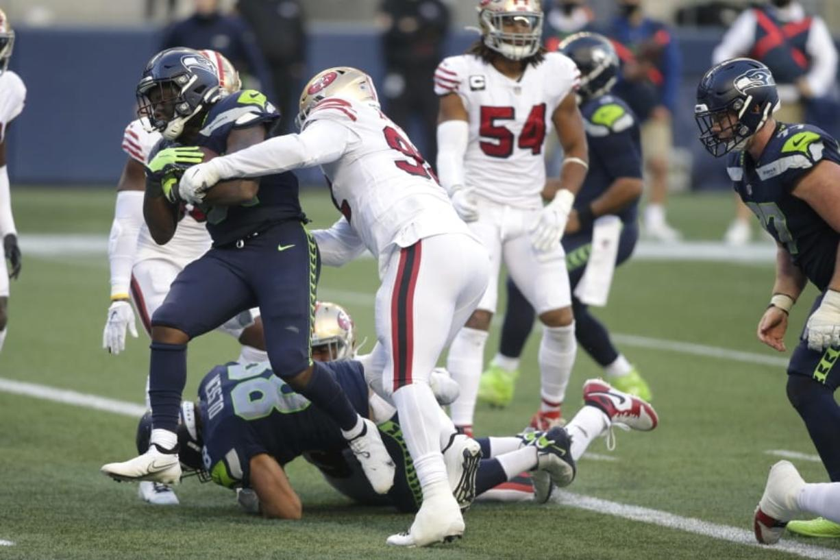 Seattle Seahawks running back DeeJay Dallas, left, scores a touchdown against the San Francisco 49ers during the second half of an NFL football game, Sunday, Nov. 1, 2020, in Seattle. The Seahawks won 37-27.