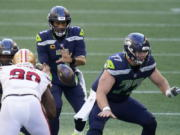 Seattle Seahawks quarterback Russell Wilson (3) takes a snap as center Ethan Pocic, right, blocks against the San Francisco 49ers during the first half of an NFL football game, Sunday, Nov. 1, 2020, in Seattle.