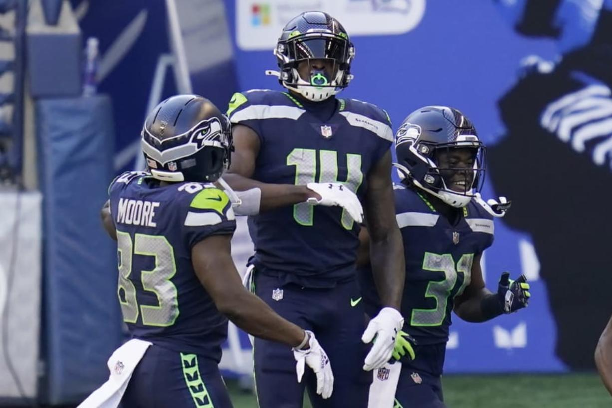 Seattle Seahawks wide receiver DK Metcalf (14) celebrates with teammates David Moore, left, and DeeJay Dallas, right, after Metcalf scored a touchdown against the San Francisco 49ers during the first half of an NFL football game, Sunday, Nov. 1, 2020, in Seattle.