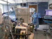 FILE - In this May 8, 2020, file photo, medical personal work on a patient in the COVID-19 Intensive Care Unit at Harborview Medical Center, which is part of Seattle-area health care system UW Medicine in Seattle.