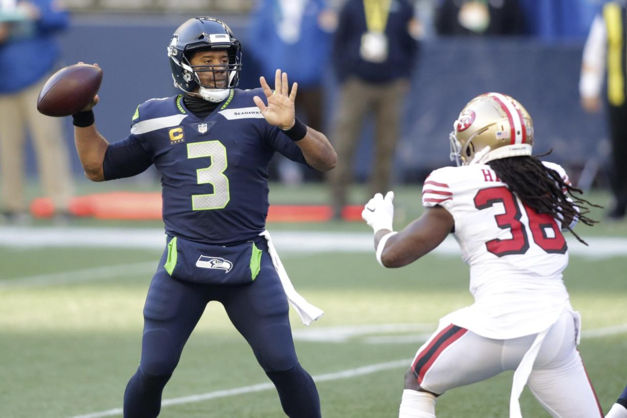 Seattle Seahawks quarterback Russell Wilson (3) makes a touchdown pass to wide receiver DK Metcalf (not shown) as San Francisco 49ers safety Marcell Harris, right, pressures during the first half of an NFL football game, Sunday, Nov. 1, 2020, in Seattle.