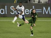 Vancouver Whitecaps forward Cristian Dajome, left, puts a shot on goal as Portland Timbers defender Jorge Villafana defends during the first half of an MLS soccer match in Portland, Ore., Sunday, Nov. 1, 2020.
