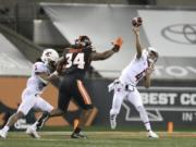 Washington State quarterback Jayden de Laura (4) throws past Oregon State inside linebacker Avery Roberts (34) and Washington State's Deon McIntosh (3) during the first half of an NCAA college football game in Corvallis, Ore., Saturday, Nov, 7, 2020.