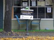 A sign for curbside pickup is shown outside the Cascadia Grill, Sunday, Nov. 15, 2020, in downtown Olympia. (AP Photo/Ted S.