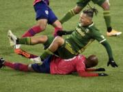 FC Dallas forward Fafa Picault, bottom, slide tackles Portland Timbers defender Pablo Bonilla, top, during the first half of an MLS soccer match in Portland, Ore., Sunday, Nov. 22, 2020.