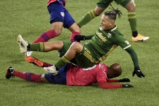 FC Dallas forward Fafa Picault, bottom, slide tackles Portland Timbers defender Pablo Bonilla, top, during the first half of an MLS soccer match in Portland, Ore., Sunday, Nov. 22, 2020.