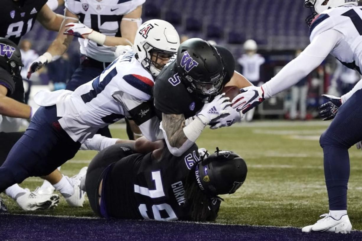 Washington's Sean McGrew (5) dives over teammate Victor Curne (79) to score against Arizona during the first half of an NCAA college football game Saturday, Nov. 21, 2020, in Seattle.