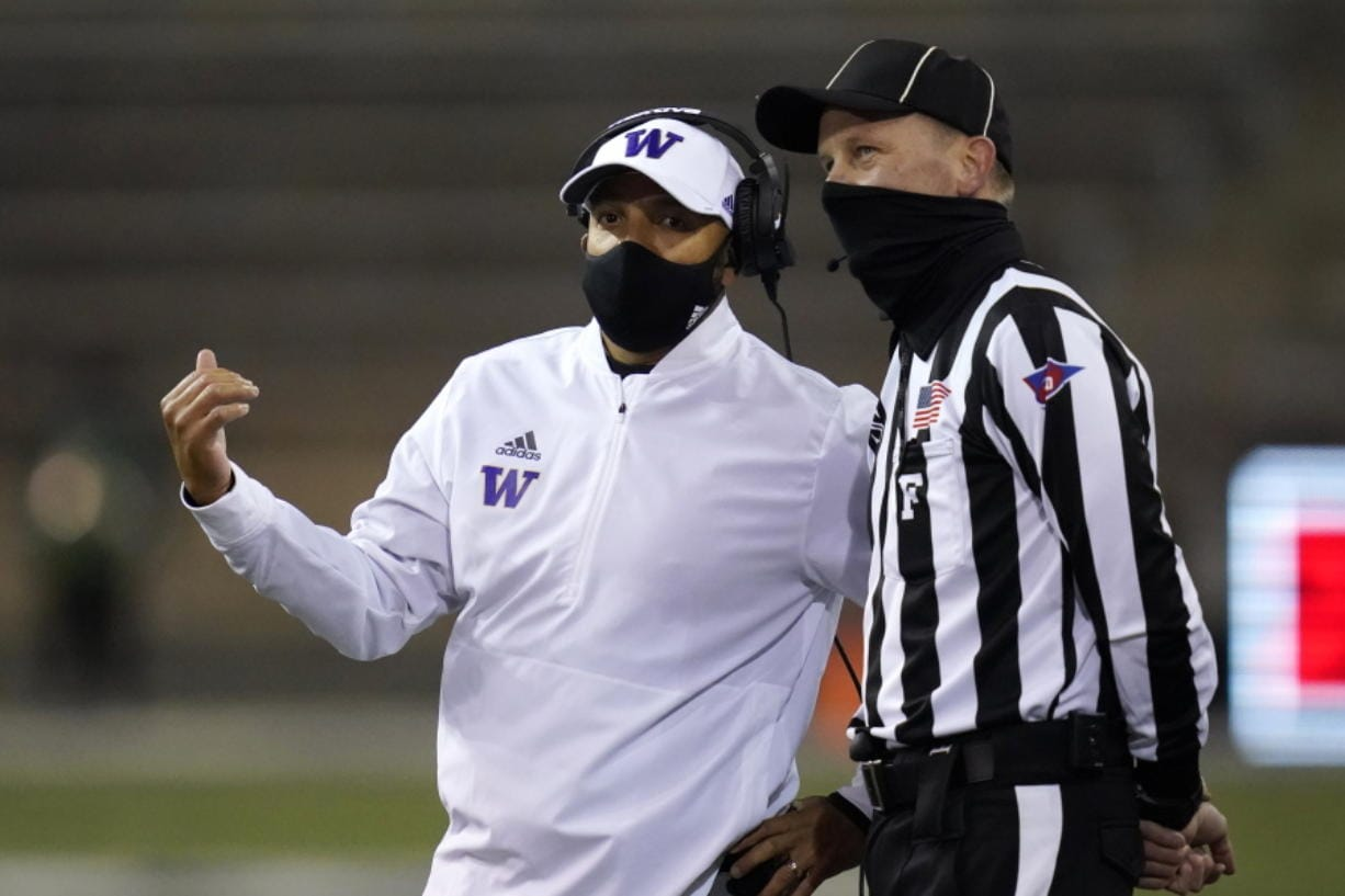 Washington coach Jimmy Lake talks with field judge Todd Migchelbrink during the first half of an NCAA college football game Saturday, Nov. 21, 2020, in Seattle.