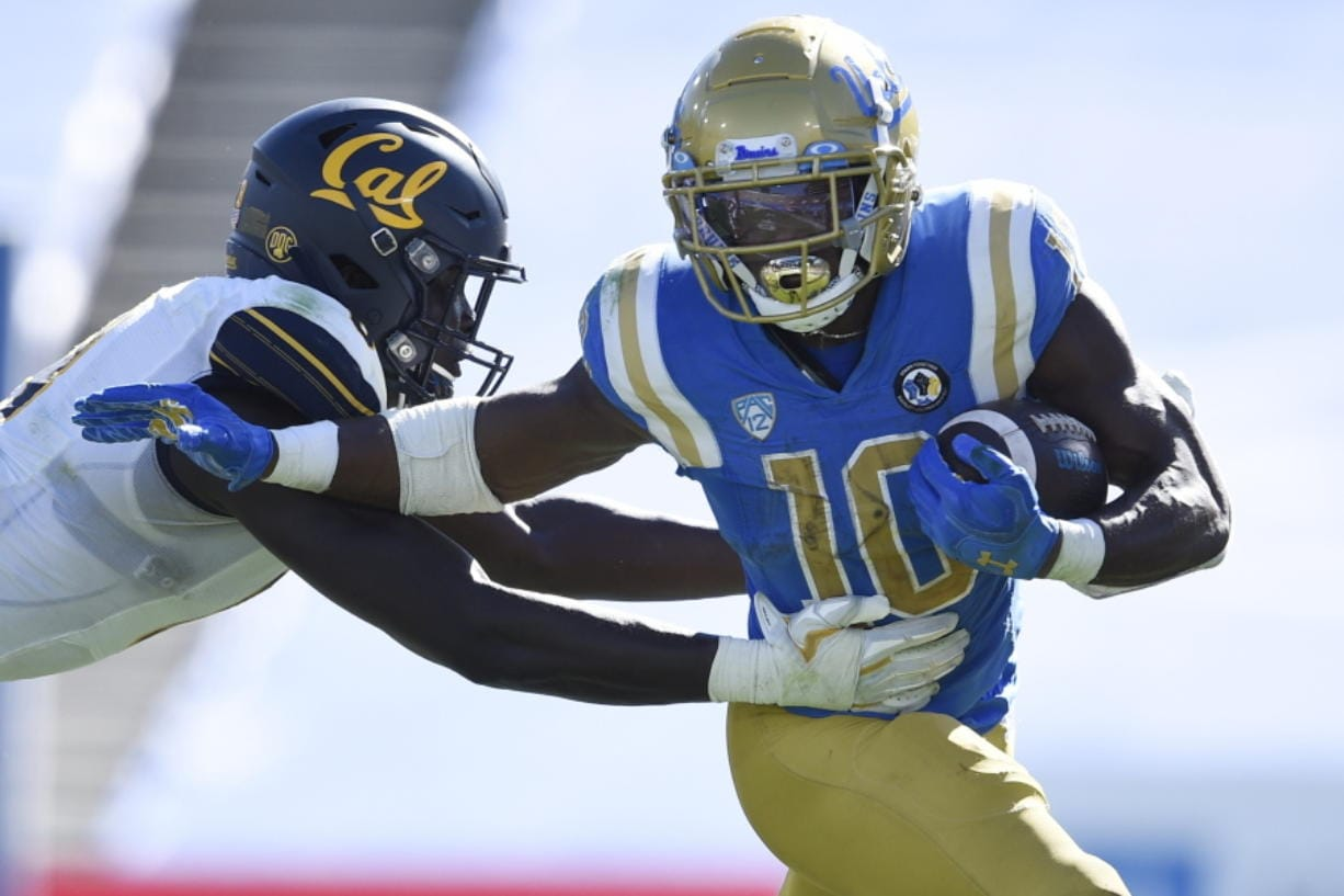 UCLA running back Demetric Felton, right, runs the ball while defended by California linebacker Kuony Deng during the second half of an NCAA college football game in Los Angeles, Sunday, Nov. 15, 2020.