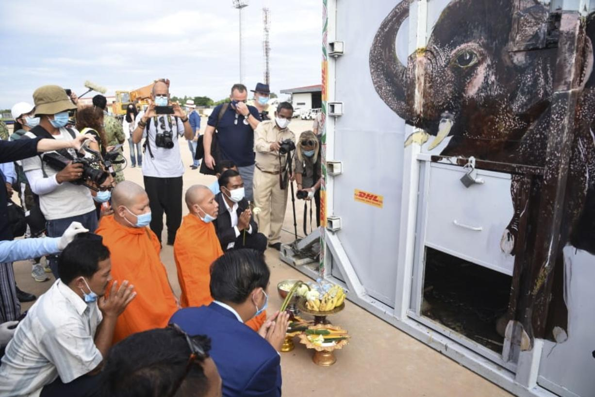 """The container holding Kaavan the elephant is blessed by monks during its arrival from Pakistan at the Siem Reap International Airport, Cambodia, Monday, Nov. 30, 2020. Kaavan, dubbed the """"world's loneliest elephant"""" after languishing alone for years in a Pakistani zoo, has arrived in Cambodia where a sanctuary with the much-needed company of other elephants awaits him."""
