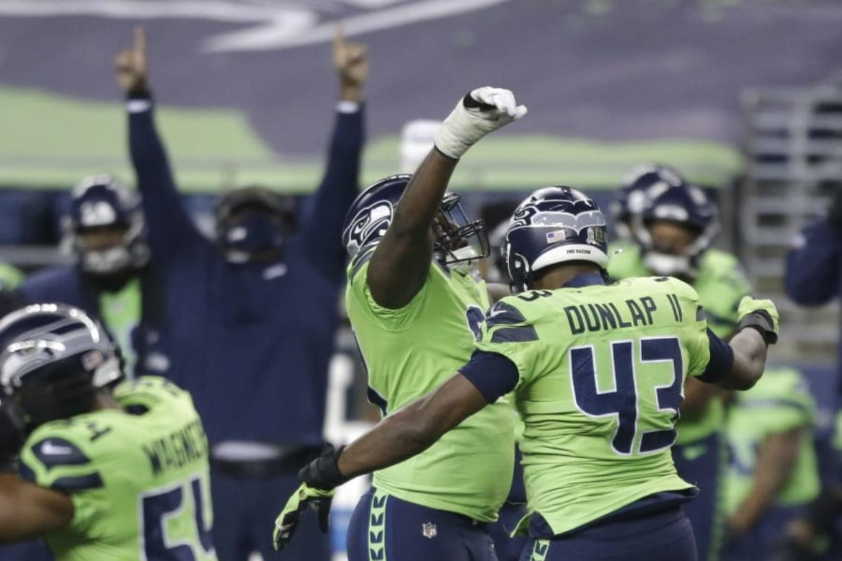 Seattle Seahawks defensive end Carlos Dunlap (43) celebrates with defensive end L.J. Collier, center-left, after Dunlap sacked Arizona Cardinals quarterback Kyler Murray late in the second half of an NFL football game, Thursday, Nov. 19, 2020, in Seattle. The Seahawks won 28-21.