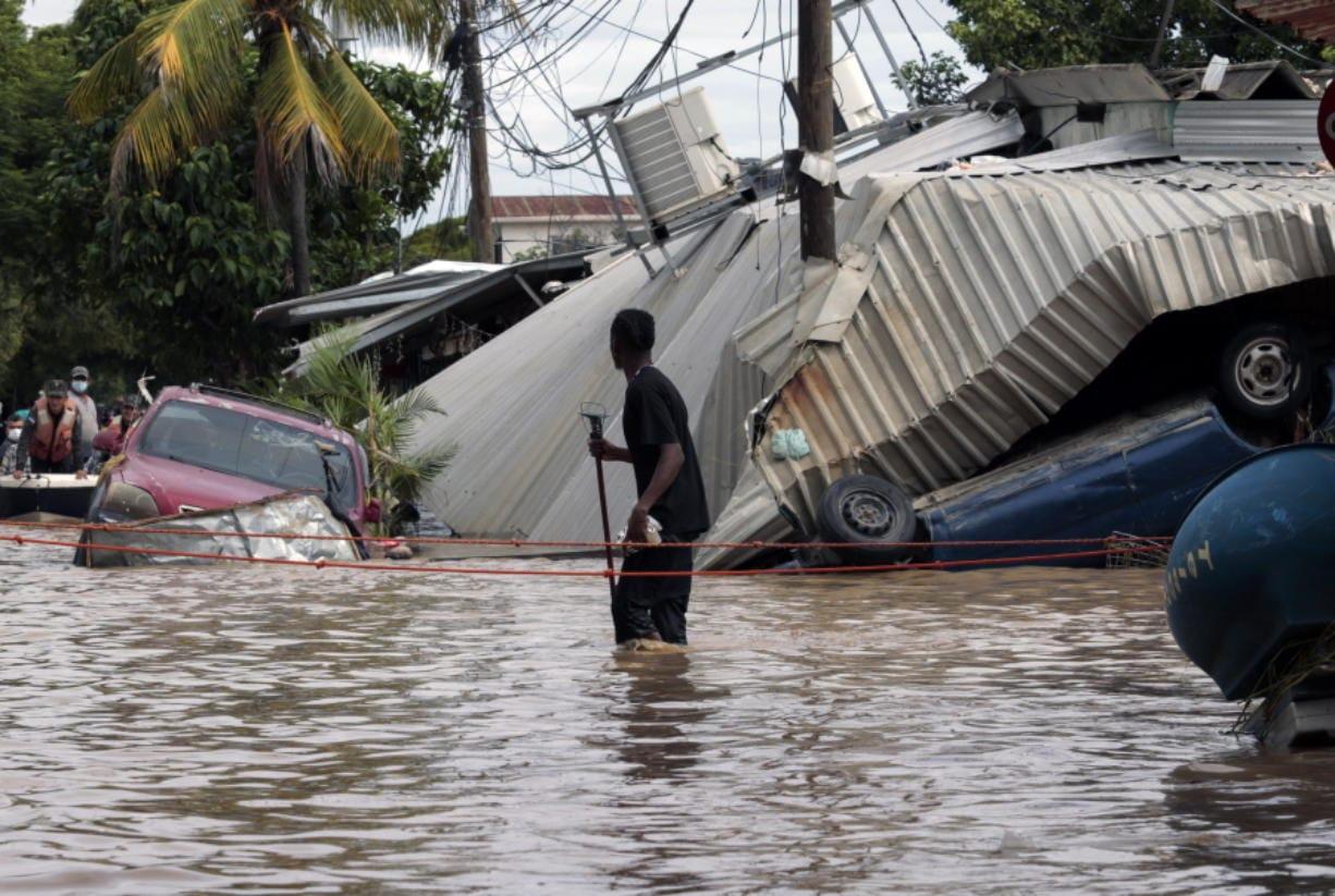 A resident walking through a flooded street Nov. 6 looks back at storm damage caused by Hurricane Eta in Planeta, Honduras.