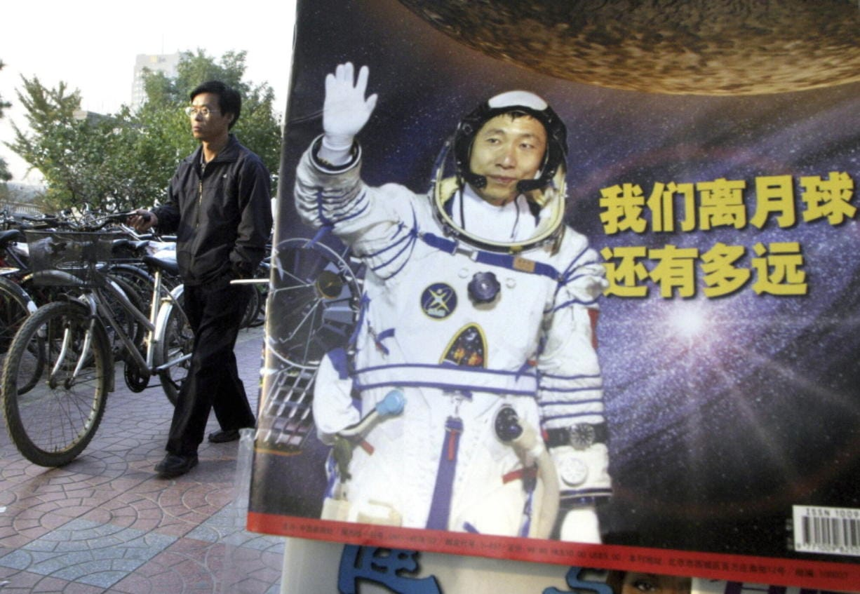"""In this photo taken Thursday, Oct 23, 2003, a man pushes his bicycle past the cover of a magazine showing China's first man in space, Yang Liwei and the Chinese characters for """"How far are we from the moon?"""" at a newsstand in Beijing, China. China's Nov. 24, 2020, trip to the moon and, presumably, back is the latest milestone in the Asian powerhouse's slow but steady ascent to the stars."""