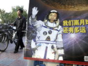 "In this photo taken Thursday, Oct 23, 2003, a man pushes his bicycle past the cover of a magazine showing China's first man in space, Yang Liwei and the Chinese characters for ""How far are we from the moon?"" at a newsstand in Beijing, China. China's Nov. 24, 2020, trip to the moon and, presumably, back is the latest milestone in the Asian powerhouse's slow but steady ascent to the stars."