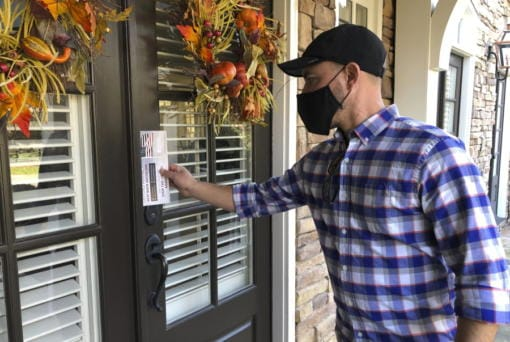 Garrett Bess, vice president of government relations and communications for the conservative activist group Heritage Action For America, leaves information at a residence in a subdivision in Milton, Ga., Friday, Nov. 20, 2020. Bess and a colleague were going door-to-door to encourage people to vote for the conservative candidates in Georgia's Jan. 5 runoff elections for U.S. Senate. The two Georgia races will decide which party controls the Senate, and that has infused voter turnout efforts by the parties and outside groups with new urgency.
