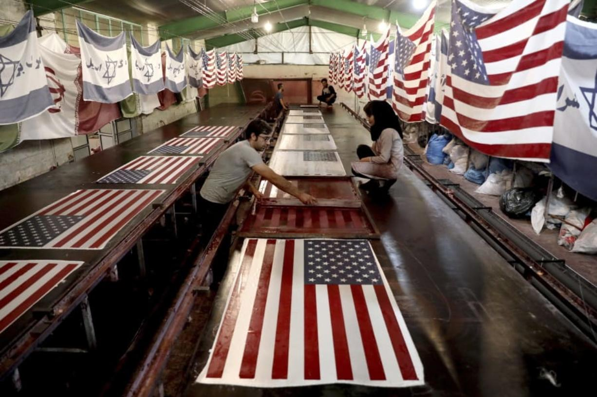 FILE - In this Saturday, Feb. 8, 2020 file photo, workers print U.S. flags using a silkscreen, at the Diba Parcham Khomein factory in Heshmatieh village, a suburb of Khomein city, in central Iran. In Iran, everything feels up in the air ahead of the U.S. election. Currency markets have frozen awaiting the vote, though the damage has been done already by President Donald Trump's maximum pressure sanctions campaign.