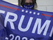 A supporter of President Donald Trump holds a flag during a news conference Tuesday, Nov. 17, 2020, in Las Vegas.