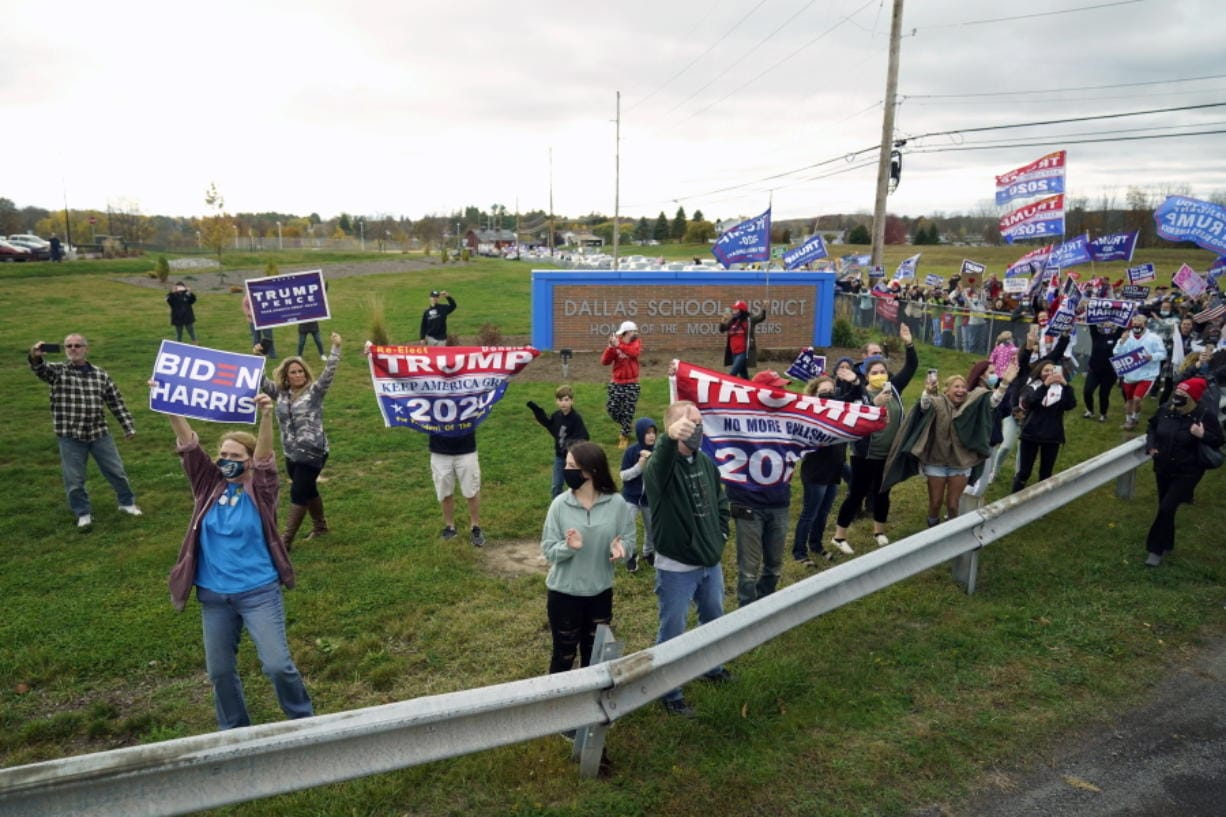 FILE - In this Oct. 24, 2020, file photo people watch as the motorcade for Democratic presidential candidate former Vice President Joe Biden arrives for a campaign rally at Dallas High School in Dallas, Pa.