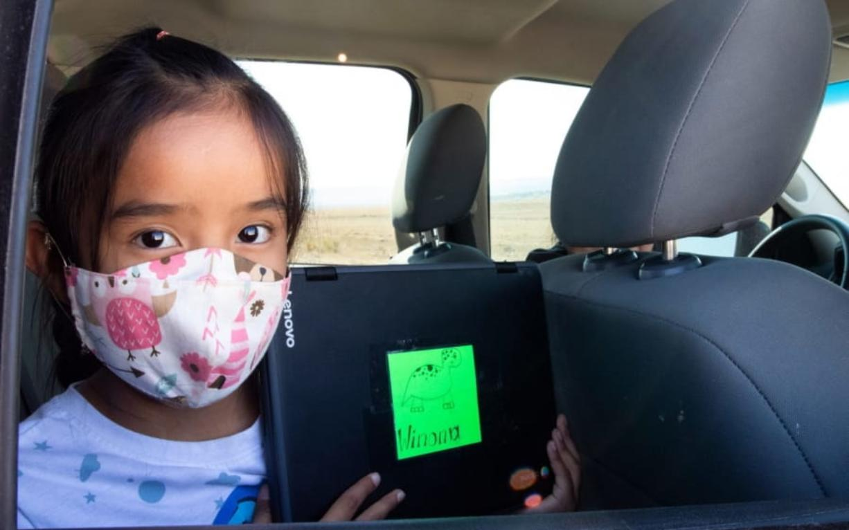 Second-grader Winona Begaye uploads homework in her family's vehicle in a dirt lot near Blue Gap, Ariz., on Sept. 25, 2020. Navajo Nation schools have remained virtual this fall because it's too dangerous to reopen their doors. To help families with no internet or poor access get online, the Pinon Unified School District outfitted school buses with Wi-Fi.