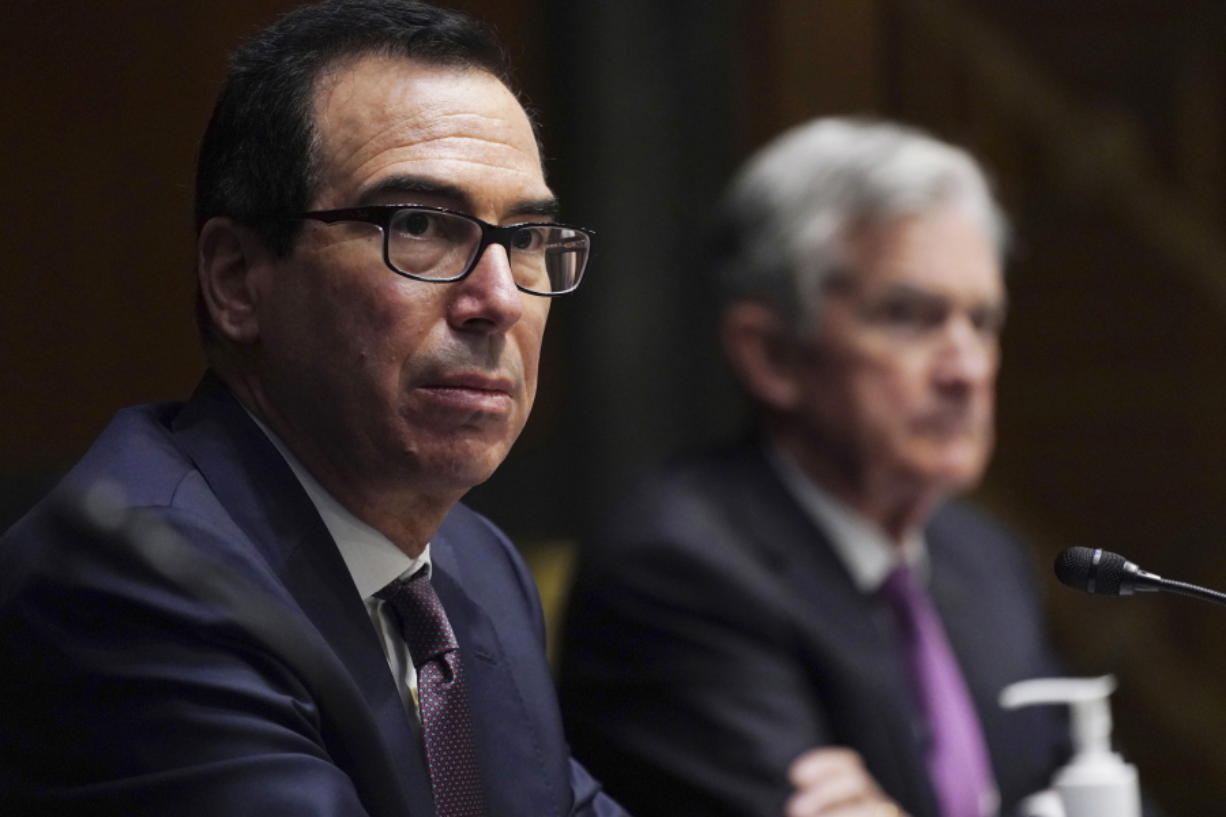FILE - In this Sept. 24, 2020 file photo, Federal Reserve Chair Jerome Powell, right, and Treasury Secretary Steve Mnuchin testify during the Senate's Committee on Banking, Housing, and Urban Affairs hearing examining the quarterly CARES Act report to Congress on Capitol Hill, in Washington. Mnuchin on Friday, Nov. 20 denied that he is trying to limit the choices President-elect Joe Biden will have to promote an economic recovery by ending several emergency loan programs being run by the Federal Reserve. Mnuchin said his decision was based on the fact that the programs were not being heavily utilized and the money could be better used by being re-allocated by Congress to provide support in other areas such as further grants to small businesses and extended unemployment assistance.  (Toni L.