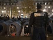 A police officer stands in front of migrants in a makeshift camp set up Monday night Nov.23, 2020 on Place de la Republique in Paris. Paris police are under government orders to explain themselves after officers were filmed tossing migrants out of tents while evacuating a makeshift camp in the French capital.