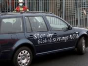 A car stand in front of the chancellery after it crashed into the front gate of the building housing German Chancellors Angela Merkel's offices in Berlin, Germany, Wednesday, Nov. 25, 2020. Slogan reads 'stop the globalization policies'.