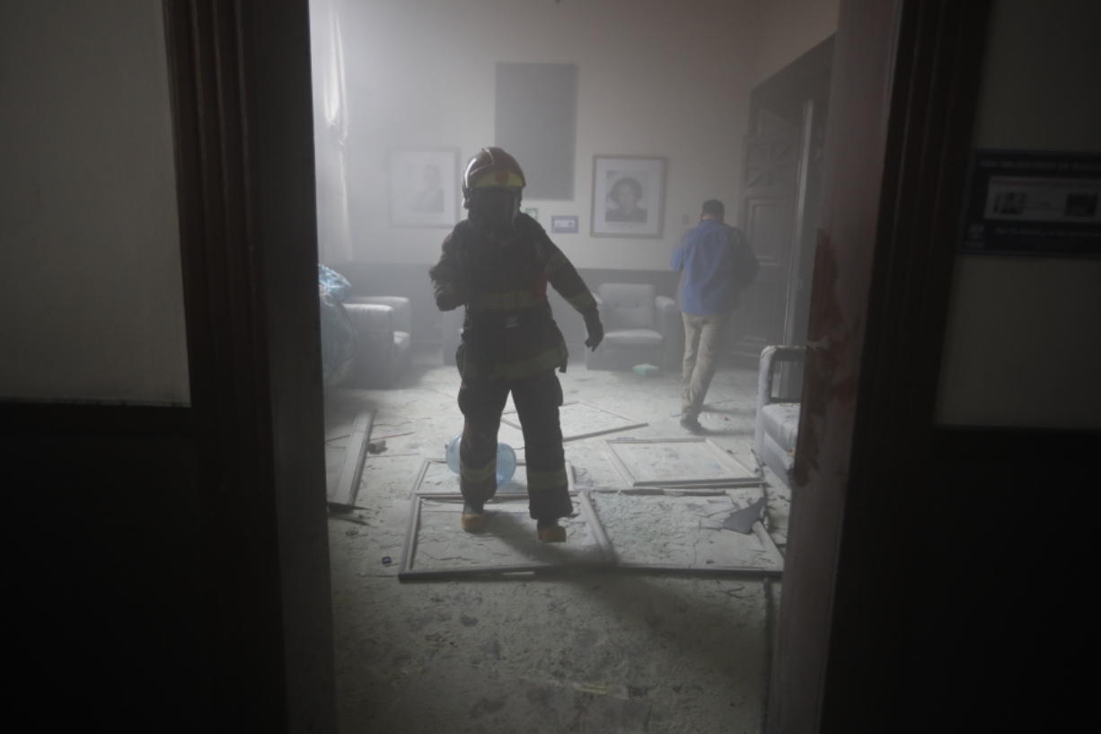 A firefighter walks inside the Congress building after protesters set the building on fire, in Guatemala City, Saturday, Nov. 21, 2020. Hundreds of protesters were protesting in various parts of the country Saturday against Guatemalan President Alejandro Giammattei and members of Congress for the approval of the 2021 budget that reduced funds for education, health and the fight for human rights.