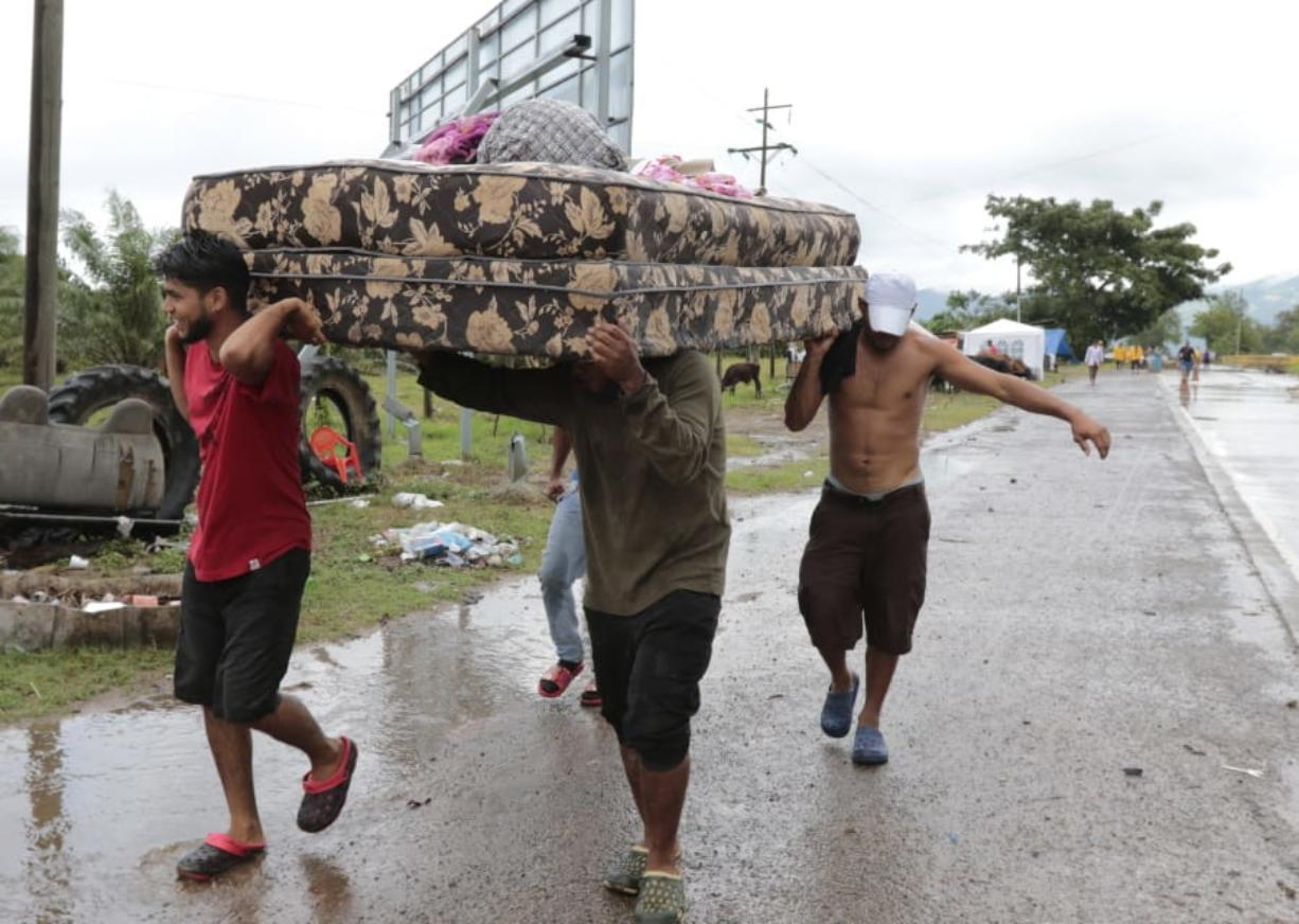Neighbors help each other as they evacuate the area before Hurricane Iota makes landfall in San Manuel Cortes, Honduras, Monday, November 16, 2020. Hurricane Iota rapidly strengthened into a Category 5 storm that is likely to bring catastrophic damage to the same part of Central America already battered by a powerful Hurricane Eta less than two weeks ago.