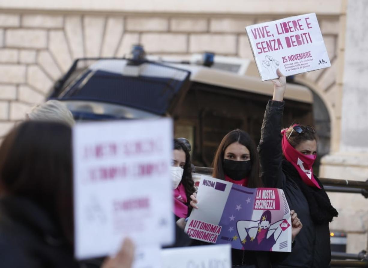 """A woman show a banner reading """"alive, free and without debts"""" during a demonstration on the occasion of International Day for the Elimination of Violence against Women, in Rome, Wednesday, Nov. 25, 2020."""
