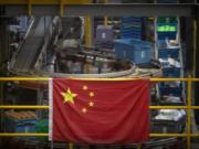 FILE - In this Nov. 11, 2020, file photo a Chinese flag hangs near an automated parcel handling line at a warehouse for an online retailer in Beijing. President Donald Trump has identified China as the country's biggest foe and the Justice Department mirrored that emphasis over the last four years with a drumbeat of cases against defendants ranging from hackers accused of targeting intellectual property to professors charged with grant fraud.