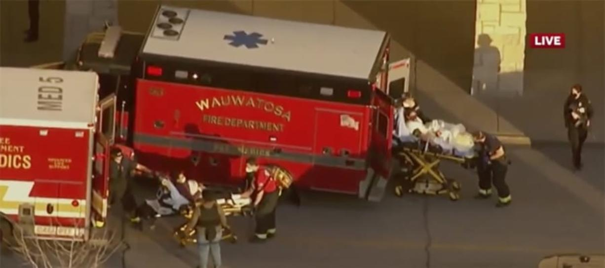 """In this image taken from video provided by WISN-TV, emergency crews place two people in waiting ambulances at the Mayfair Mall in Wauwatosa, Wis., on Friday, Nov. 20, 2020. A police dispatcher says officers are responding to """"a very active situation"""" at the suburban Milwaukee mall."""