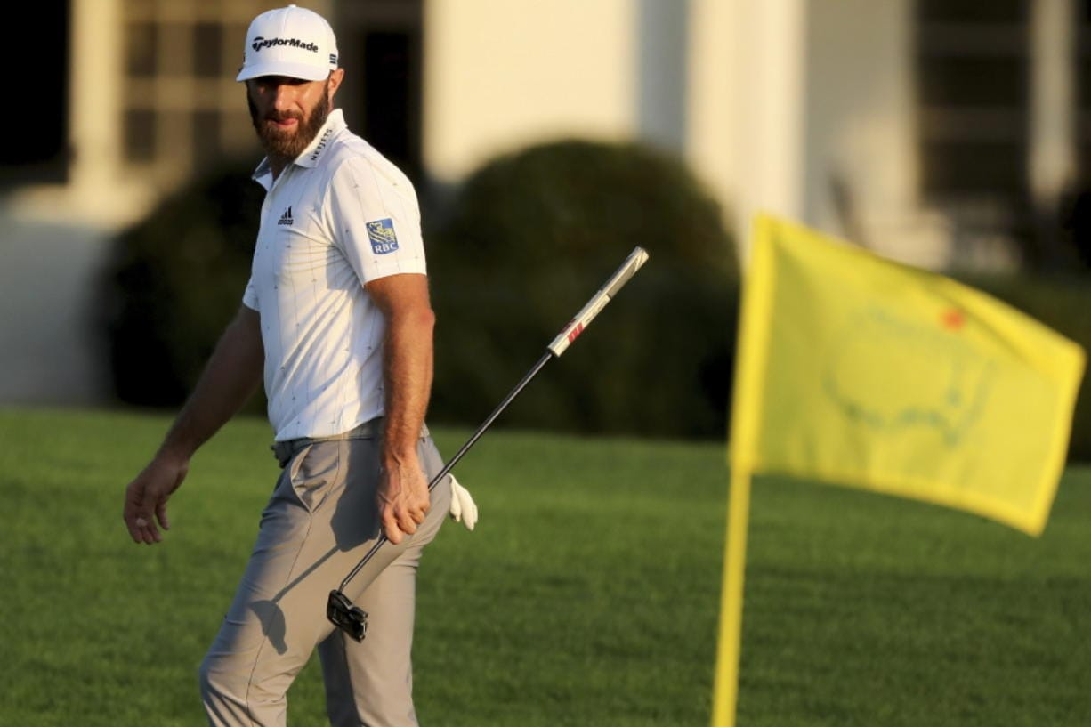 Dustin Johnson looks over his shot on the 18th green next to the Masters yellow flag during the third round of the Masters golf tournament Saturday, Nov. 14, 2020, in Augusta, Ga.