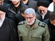 FILE - In this photo released by the official website of the Office of the Iranian Supreme Leader, Gen. Esmail Ghaani, newly appointed commander of Iran's Revolutionary Guards Quds Force, weeps while praying over the coffin of the force's previous head Gen. Qassem Soleimani at the Tehran University Campus in Tehran, Iran, Monday, Jan. 6, 2020.  On Friday, Nov. 20, two Iraqi officials say Iran has instructed allies in the Middle East to be on high alert and avoid provoking tensions with the U.S. that could give an outgoing Trump Administration cause to launch attacks in his final weeks in office.