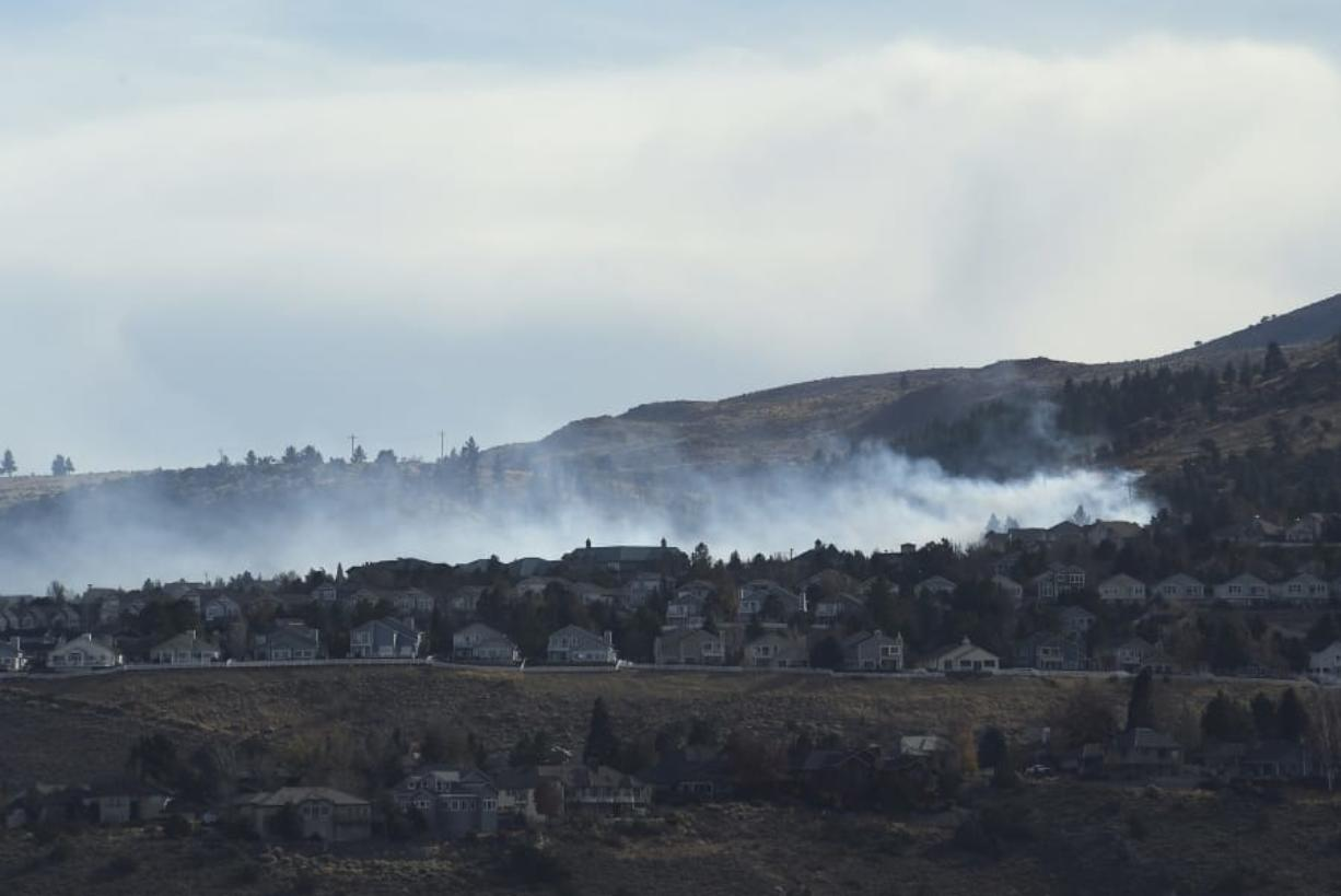 A fire is seen burning in the Caughlin Ranch area of Reno, Nev., on Tuesday, Nov. 17, 2020. Firefighters are battling a wildfire in southwest Reno that is threatening some homes in dangerously high winds. Dozens of residences were being evacuated on the edge of the Sierra foothills.