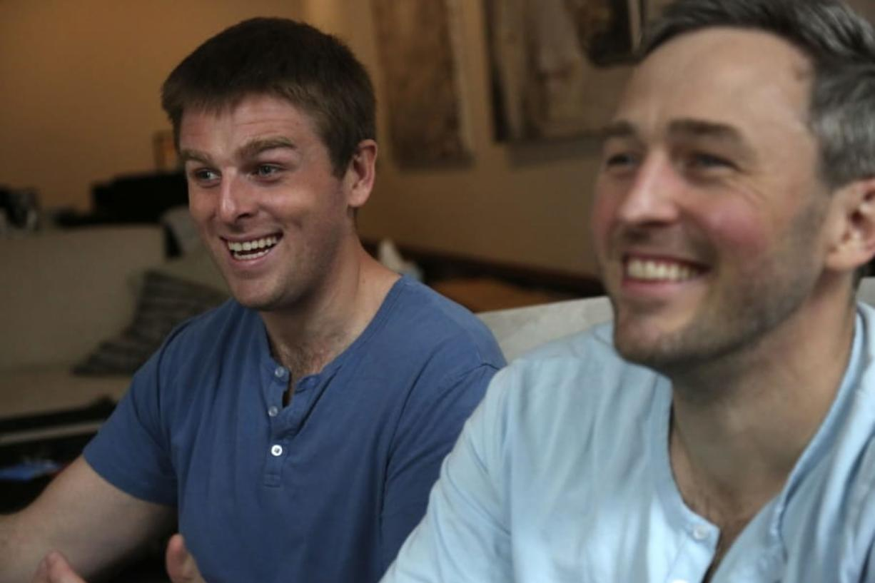 Brothers, Bryan, left, and Bradford Manning, laugh as they tell the origin story of their clothing company, Two Blind Brothers, in their New York City loft on Friday, Oct. 23, 2020. The brothers who've lost much of their vision to a rare degenerative eye disorder began their company in 2016 and have donated all of their profits, more than $700,000, to preclinical research trials to help cure blindness.