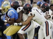 FILE - In this Oct. 5, 2019, file photo, UCLA running back Joshua Kelley, left, is tackled by Oregon State linebackers Hamilcar Rashed Jr. (9) and John McCartan (6) during the first half of an NCAA college football game in Pasadena, Calif. While the offense is still coming together with presumed starting quarterback Tristan Gebbia, it's Oregon State's defense that should worry opponents.