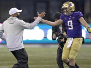 Washington head coach Jimmy Lake, left, greets starting quarterback Dylan Morris (9) after Washington beat Oregon State 27-21 in an NCAA college football game, Saturday, Nov. 14, 2020, in Seattle. The game was Lake's first since he was named head coach. (AP Photo/Ted S.